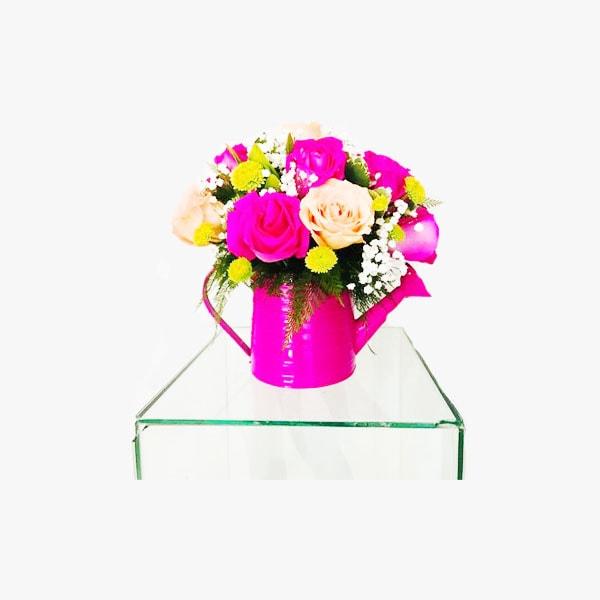 Arreglo redondo compuesto con rosas de colores en regadera