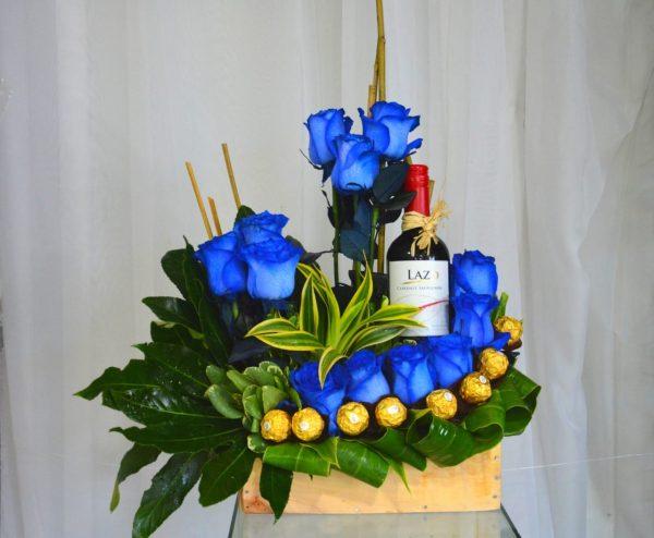 Arreglo de 12 Rosas Azules con Chocolates y Vino en Base Especial de Madera